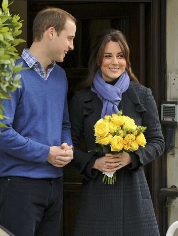 Britain's Prince William stands next to his wife, the Duchess of Cambridge, nee Kate Middleton, as she leaves the King Edward VII Hospital in London on Thursday, Dec. 6, 2012. The duchess was treated for a severe form of morning sickness in the early stages of her pregnancy. (AP Photo/Andrew Matthews, PA)