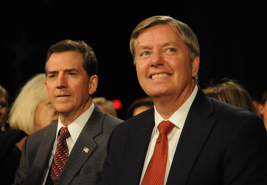 Sens. Lindsey Graham (right) and Jim DeMint, South Carolina Republicans, prepare to watch the CBS News/National Journal foreign policy debate at the Benjamin Johnson Arena in Spartanburg, S.C., on Saturday, Nov. 12, 2011. (AP Photo/Richard Shiro)