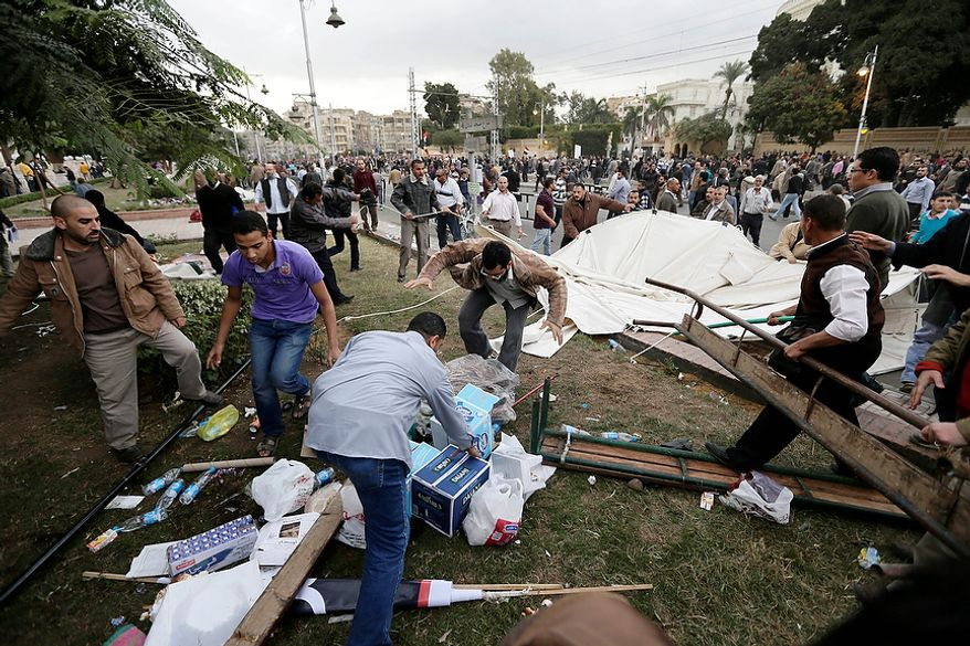 Supporters of Egyptian President Mohammed Morsi remove tents of opposition protesters outside the presidential palace in Cairo on Dec. 5, 2012. Supporters of Morsi and opponents clashed outside the presidential palace, beginning when thousands of Islamist supporters of Morsi descended on the area around the palace where some 300 of his opponents were staging a sit-in. (Associated Press)