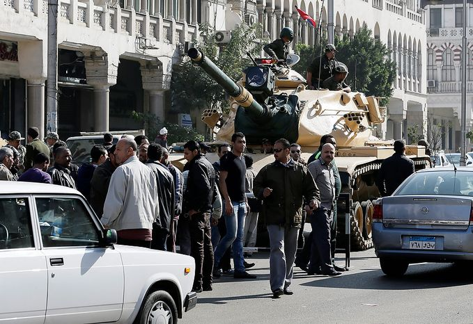An Egyptian Army tank deploys near the presidential palace to secure the site of overnight clashes between supporters and opponents of President Mohammed Morsi in Cairo on Dec. 6, 2012. The Egyptian army has deployed tanks outside the presidential palace in Cairo following clashes between supporters and opponents of Morsi that left several people dead and hundreds wounded. (Associated Press)