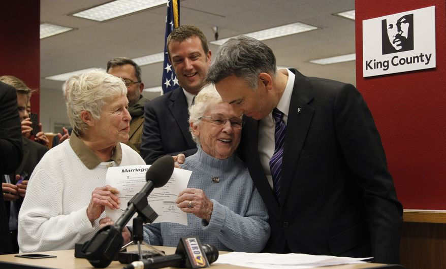 King County Executive Dow Constantine (right) embraces Pete-e Petersen as her partner, Jane Abbott Lighty, looks on after Mr. Constantine issued the two women the first marriage license for a same-sex couple, on Thursday, Dec. 6, 2012, in Seattle. (AP Photo/Elaine Thompson)