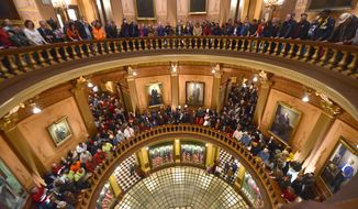 **FILE** Pro-union demonstrators crowd the Rotunda of the Michigan Capitol in Lansing to chant against right-to-work legislation on Dec. 5, 2012. (Associated Press/Detroit News)