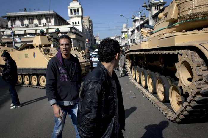 Egyptian Army tanks deploy near the presidential palace in Cairo on Dec. 6, 2012, to secure the site of overnight clashes between supporters and opponents of President Mohammed Morsi. (Associated Press)