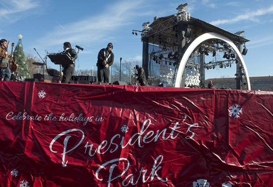 Members of the stage crew set up microphones, guitars and other gear on Dec. 6, 2012, for the lighting of the National Christmas tree on the Ellipse in downtown D.C. later that evening. (Barbara L. Salisbury/The Washington Times)