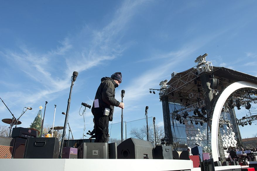 A member of the stage crew sets microphones in place on Dec. 6, 2012, during setup and rehearsal for the lighting of the National Christmas tree on the Ellipse in downtown D.C. later that evening. (Barbara L. Salisbury/The Washington Times)