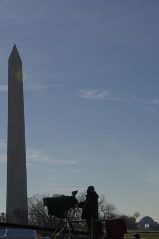 A television cameraman is silhouetted in between the Washington Monument and the Jefferson Memorial on Dec. 6, 2012, as he films the rehearsal for the lighting of the National Christmas tree on the Ellipse in downtown D.C. later that evening. (Barbara L. Salisbury/The Washington Times)
