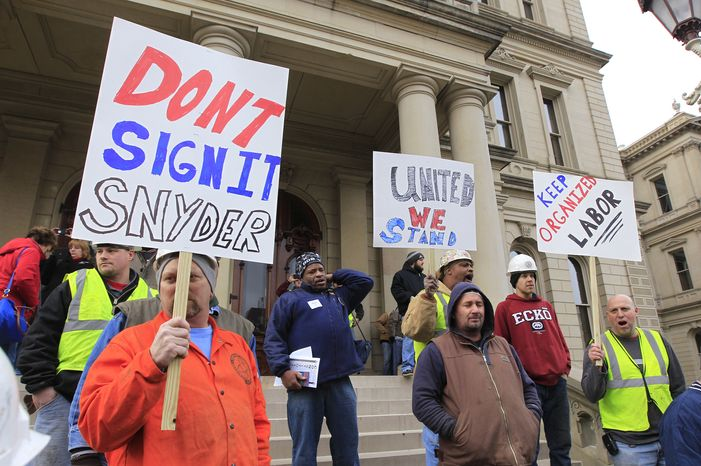 Union workers hold up signs during a rally outside the Capitol in Lansing, Mich., on Thursday, Dec. 6, 2012, as Republican lawmakers introduced right-to-work legislation in the waning days of the legislative session. (AP Photo/Carlos Osorio)
