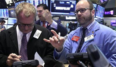 Traders Douglas Glander (left) and Peter Mancuso (right) work on the floor of the New York Stock Exchange on Thursday, Dec. 6, 2012. (AP Photo/Richard Drew)
