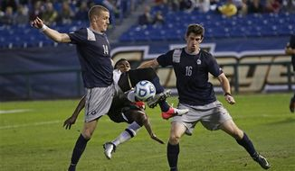 Maryland's Mikias Eticha, center, tries to shoot the ball between the defense of Georgetown's Cole Seiler, left, and Jimmy Nealis, right, in the second half of their NCAA College Cup men's championship semifinal soccer match at Regions Park, Friday, Dec. 7, 2012, in Hoover, Ala. Georgetown won in penalty kicks. (AP Photo/Dave Martin) ** FILE **