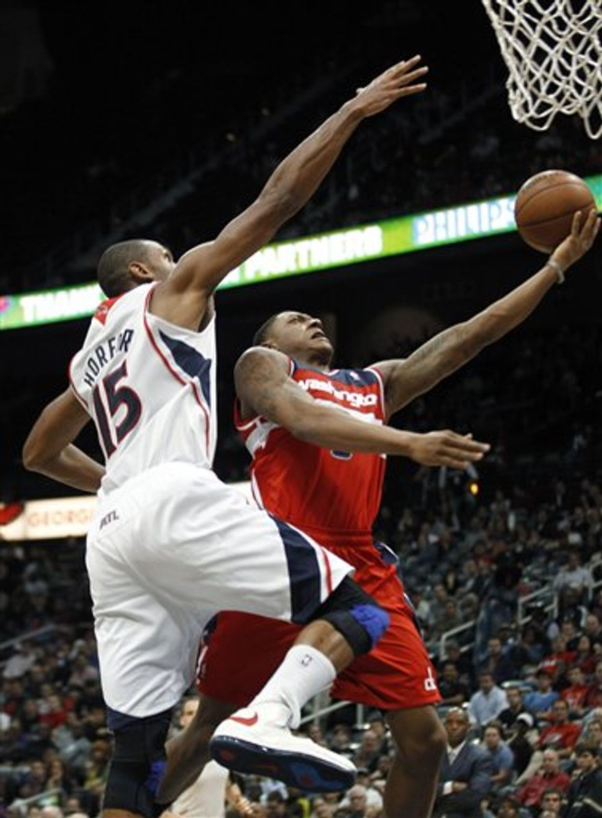 Washington Wizards guard Bradley Beal is fouled as he drives to the basket by Atlanta Hawks center Al Horford (15) in the second half of an NBA basketball game Friday, Dec. 7, 2012, in Atlanta. Atlanta won 104-95. (AP Photo/John Bazemore)