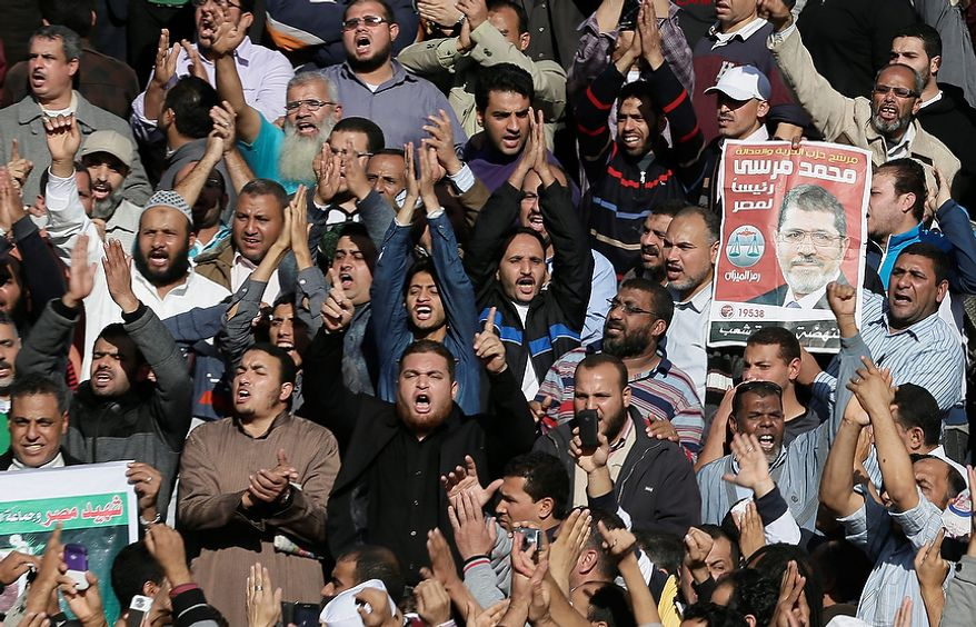 "Supporters of Muslim Brotherhood and Egyptian President Mohammed Morsi, pictured at right, chant slogans during the funeral of three victims who were killed during Wednesday's clashes outside Al-Azhar mosque, the highest Islamic Sunni institution, Friday, Dec. 7, 2012. During the funeral, thousands Islamist mourners chanted, ""with blood and soul, we redeem Islam,"" pumping their fists in the air. ""Egypt is Islamic, it will not be secular, it will not be liberal,"" they chanted as they walked in a funeral procession that filled streets around Al-Azhar mosque.  (AP Photo/Hassan Ammar)"