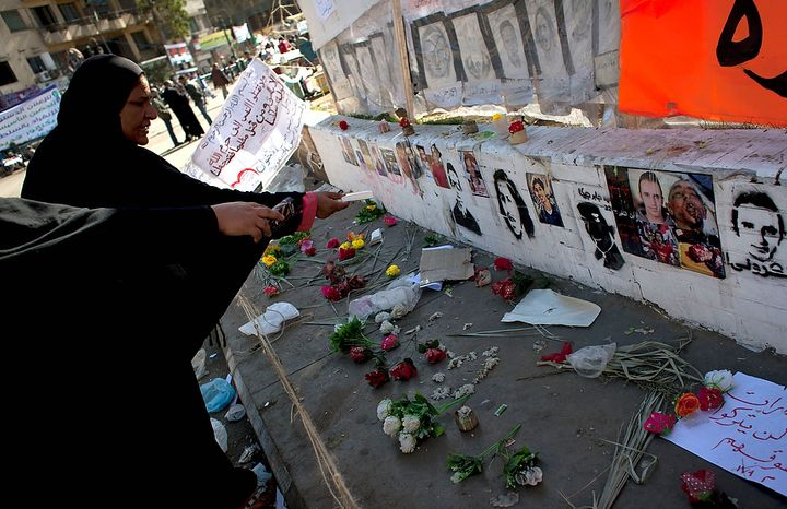 """Two Egyptian women protesters pay their respects in front of a spot designated for pictures of protesters killed during the Egyptian revolution and verses of Quran that reads """"do not kill the soul that God restricted you from killing without justice,"""" at Tahrir Square, Cairo, Egypt, Friday, Dec. 7, 2012. Thousands of Egyptians took to the streets after Friday midday prayers in rival rallies and marches across Cairo, as the standoff deepened over what opponents call the Islamist president's power grab, raising the specter of more violence. (AP Photo/Nasser Nasser)"""