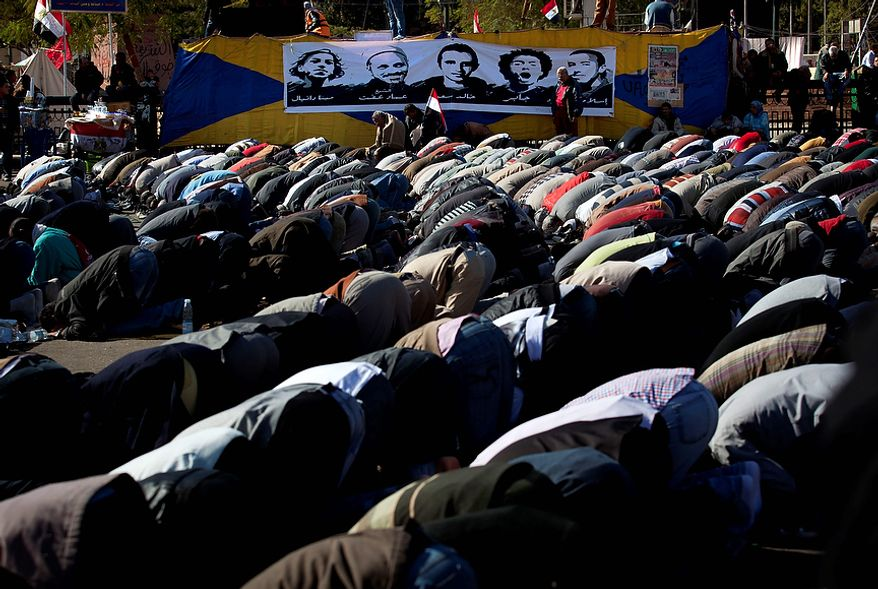 """Egyptian protesters opposing president Mohammed Morsi attend Friday prayers beneath with a poster depicting protesters killed in the Egyptian revolution, at Tahrir Square, Cairo, Egypt, Friday, Dec. 7, 2012. Arabic on the poster reads their names from right """"Islam, Jaber, Khalid Said, Emad Effat and Mina Daniel."""" Thousands of Egyptians took to the streets after Friday midday prayers in rival rallies and marches across Cairo, as the standoff deepened over what opponents call the Islamist president's power grab, raising the specter of more violence. (AP Photo/Nasser Nasser)"""