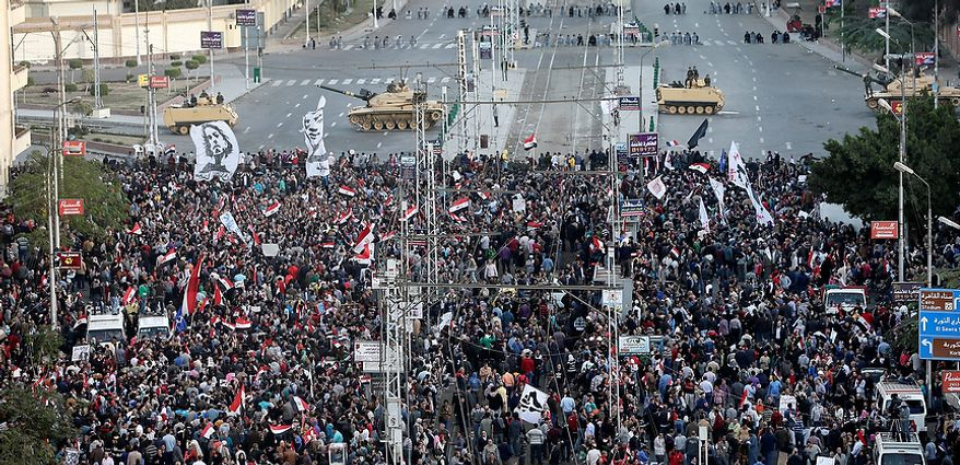 Egyptian army tanks secure the perimeter of the presidential palace while protesters gather chanting anti president Mohammed Morsi slogans, in Cairo, Egypt, Friday, Dec. 7, 2012. Egypt's political crisis spiraled deeper into bitterness and recrimination Friday as thousands of Islamist backers of the president vowed vengeance at a funeral for two men killed in bloody clashes earlier this week and large crowds of the president's opponents marched on his palace to increase pressure after he rejected their demands. (AP Photo/Hassan Ammar)