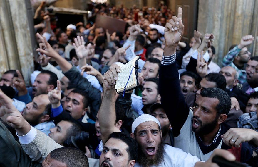 """Muslim Brotherhood and Egyptian President Morsi supporters chant slogans during a funeral of three victims who were killed during Wednesday's clashes outside Al Azhar mosque, the highest Islamic Sunni institution, Friday, Dec. 7, 2012. During the funeral, thousands Islamist mourners chanted, """"with blood and soul, we redeem Islam,"""" pumping their fists in the air. """"Egypt is Islamic, it will not be secular, it will not be liberal,"""" they chanted as they walked in a funeral procession that filled streets around Al-Azhar mosque. Thousands of Egyptians took to the streets after Friday midday prayers in rival rallies and marches across Cairo, as the standoff deepened over what opponents call the Islamist president's power grab, raising the specter of more violence. (AP Photo/Hassan Ammar)"""