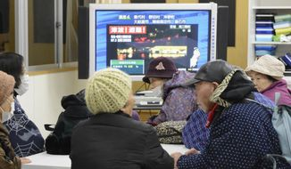 Tsunami evacuees watch TV news flashing a tsunami warning at their shelter Takata Junior High School that stands on a higher ground in Rikuzentakata in Iwate Prefecture on Dec. 7, 2012, after a strong earthquake struck off the coast of northeastern Japan. It is the same region that was hit by a massive earthquake and tsunami last year. (Associated Press/Kyodo News)