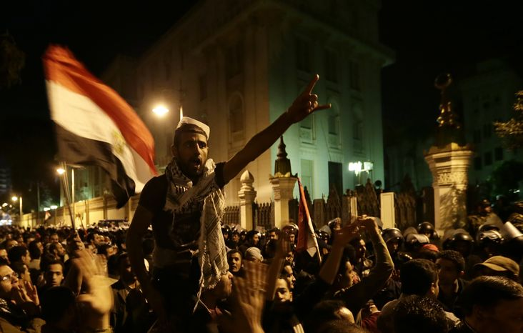 Egyptian protesters chant slogans against the Muslim Brotherhood and Egyptian President Mohammed Morsi outside the presidential palace in Cairo on Dec. 7, 2012, after they broke a barbed wire barricade keeping them from getting closer to the palace. Egypt's political crisis spiraled deeper into bitterness and recrimination as thousands of Islamist backers of the president vowed vengeance at a funeral for men killed in bloody clashes earlier in the week and large crowds of the president's opponents marched on his palace to increase pressure after he rejected their demands. (Associated Press