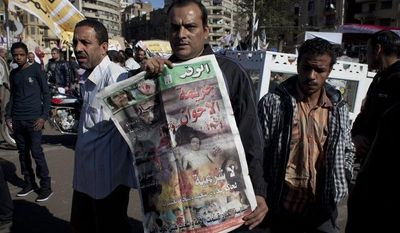 """An Egyptian protester carries a copy of Al Wafd newspaper front page that reads in Arabic, """"the brotherhood's crime, no legitimacy for a governor who is against his people,"""" during a protest against President Mohammed Morsi near the presidential palace in Cairo on Dec. 7, 2012. (Associated Press)"""