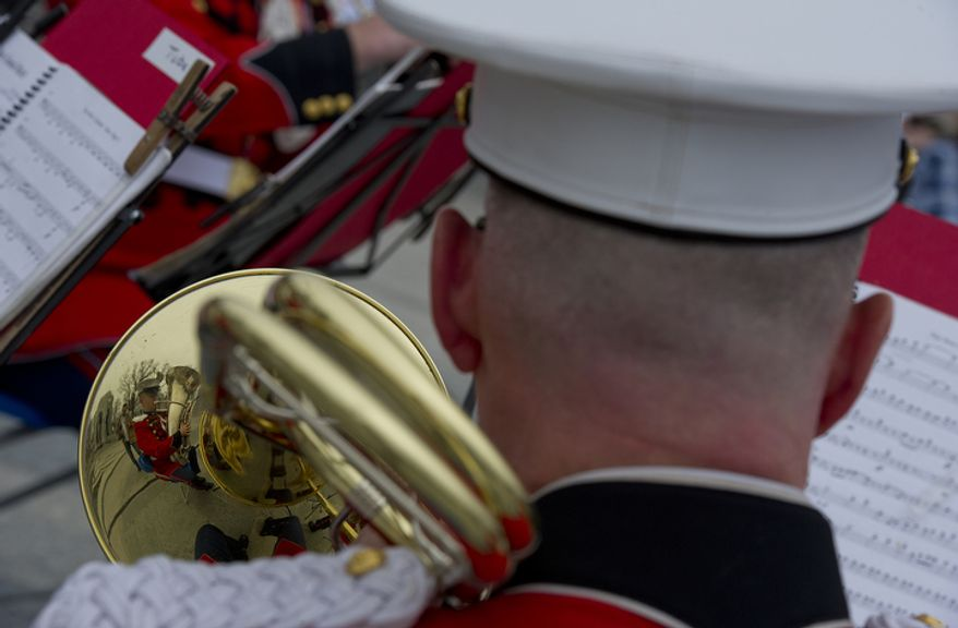 Gunnery Sgt. Chris Clark is reflected in his trombone as he plays with the Marine Band brass quintet at the National Pearl Harbor Remembrance Day ceremony on Friday, Dec. 7, 2012, at the National World War II Memorial in Washington. (The Washington Times)