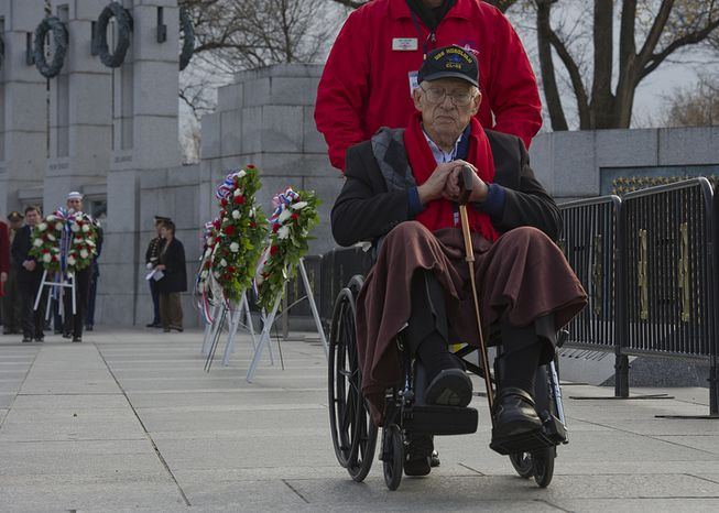 Jim Hardwick of Dallas, Texas is wheeled away after laying a wreath at the National World War II Memorial in Washington, D.C. on Friday, Dec. 7, 2012 during the National Pearl Harbor Remembrance Day ceremony. Mr. Hardwick, who was 17 when he enlisted in the U.S. Navy, served in the Pacific in World War II. (Barbara L. Salisbury/The Washington Times)