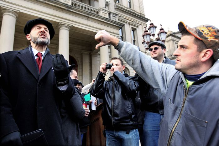 David Dudenhoefer, a right-to-work supporter, is met with opposition from union employees Thursday at the Capitol in Lansing, Mich. Michigan has pushed ahead with a bill to make the labor stronghold a right-to-work state. (Associated Press)