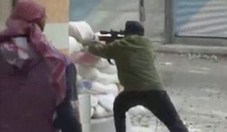 This image from amateur video that AP obtained from Ugarit News has been authenticated based on its contents and other AP reporting and shows a rebel firing a weapon around a corner at Syrian government forces in Damascus, Syria, on Dec. 7, 2012. Fighting around the Syrian capital intensified as rebels press a battle they hope will lead to the collapse of President Bashar Assad's regime after 20 months of conflict. (Associated Press/Ugarit News via AP Video)
