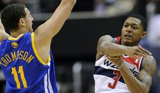 Washington Wizards guard Bradley Beal (3) passes the ball past Golden State Warriors guard Klay Thompson (11) during the first half of an NBA basketball game, Saturday, Dec. 8, 2012, in Washington. (AP Photo/Nick Wass)