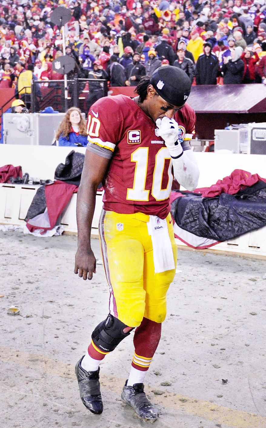 Redskins quarterback Robert Griffin III walks on the sideline with a brace on his right knee after a hit from Haloti Ngata took him out of the game. (Preston Keres/The Washington Times)