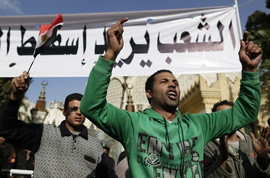 """Egyptian protesters chant slogans against the Muslim Brotherhood and President Mohammed Morsi outside the presidential palace under a banner with a defaced picture of Mr. Morsi and Arabic that reads, """"The people want to bring down the regime,"""" in Cairo on Saturday, Dec. 8, 2012. (AP Photo/Hassan Ammar)"""