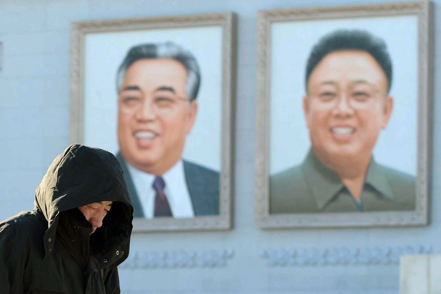A North Korean walks in front of portraits of North Korean founder Kim Il-sung (left) and late leader Kim Jong-ll in Kim Il-sung Square in Pyongyang, North Korea, on Sunday, Dec. 9, 2012. (AP Photo/Kyodo News)