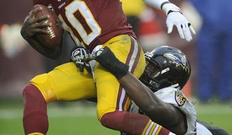 Baltimore Ravens defensive end Arthur Jones pulls Washington Redskins quarterback Robert Griffin III to the ground during the second half of an NFL football game in Landover, Md., Sunday, Dec. 9, 2012. (AP Photo/Nick Wass)