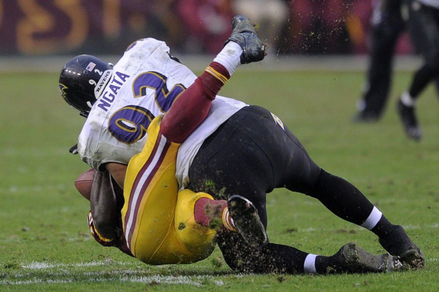 Washington Redskins quarterback Robert Griffin III (10) injures his right leg he's tackled by Baltimore Ravens defensive end Haloti Ngata (92) in the fourth quarter at FedEx Field, Landover, Md., Dec. 9, 2012. (Preston Keres/Special to The Washington Times)