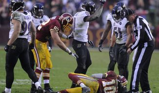 Baltimore Ravens strong safety Bernard Pollard (31) calls to the Redskins sideline as quarterback Robert Griffin III (10) lies injured on the field in the fourth quarter at FedEx Field, Landover, Md., Dec. 9, 2012. (Preston Keres/Special to The Washington Times)