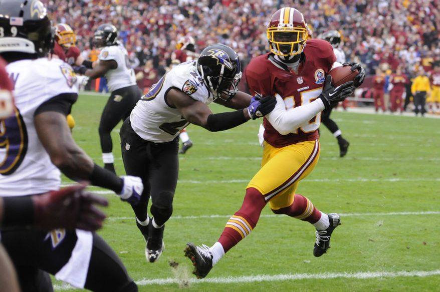 Washington Redskins wide receiver Josh Morgan (15) hauls in a 4-yard touchdown pass in front of Baltimore Ravens free safety Ed Reed (20) for the first score of the gam at FedEx Field, Landover, Md., Dec. 9, 2012. (Preston Keres/Special to The Washington Times)