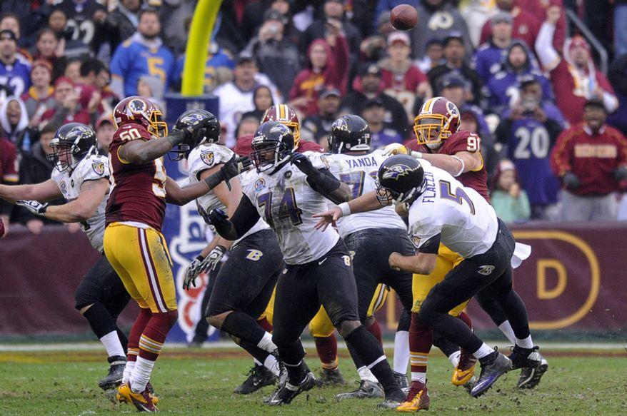 Washington Redskins outside linebacker Ryan Kerrigan (91) hits Baltimore Ravens quarterback Joe Flacco (5) forcing an interception in the third quarter at FedEx Field, Landover, Md., Dec. 9, 2012. (Preston Keres/Special to The Washington Times)