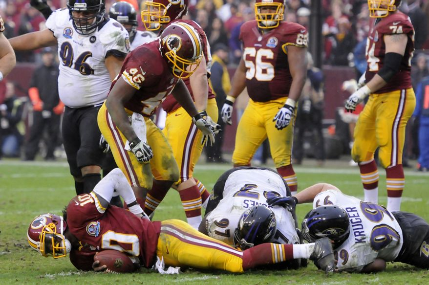 Washington Redskins quarterback Robert Griffin III (10) lies on the ground after being sacked deep in Redskins territory in the fourth quarter at FedEx Field, Landover, Md., Dec. 9, 2012. (Preston Keres/Special to The Washington Times)