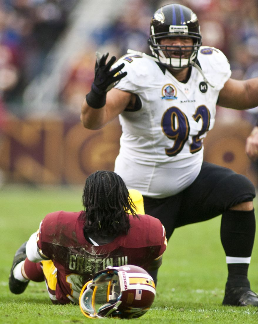 Washington Redskins quarterback Robert Griffin III (10) is lays on the ground after getting hit hard by Baltimore Ravens defensive end Haloti Ngata (92) in the first half at FedEx Field in Landover Md., on Sunday, December 9, 2012. (Craig Bisacre/The Washington Times)