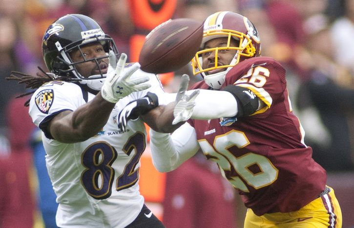 Washington Redskins cornerback Josh Wilson (26) breaks up a pass to Baltimore Ravens wide receiver Torrey Smith (82) in the first half against the Baltimore Ravens at FedEx Field in Landover Md., on Sunday, December 9, 2012. (Craig Bisacre/The Washington Times)