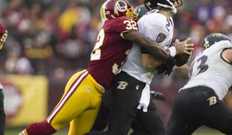 Washington Redskins defensive back Jordan Pugh (32) sacks Baltimore Ravens quarterback Joe Flacco (5) in the second half at FedEx Field in Landover Md., on Sunday, December 9, 2012. Washington Redskins won 31 to 28. (Craig Bisacre/The Washington Times)