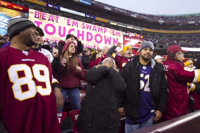 Fans celebrate after Washington Redskins quarterback Kirk Cousins (12) runs in the game tying touchdown in the fourth quarter against the Baltimore Ravens at FedEx Field in Landover Md., on Sunday, December 9, 2012. Washington Redskins won 31 to 28. (Craig Bisacre/The Washington Times)
