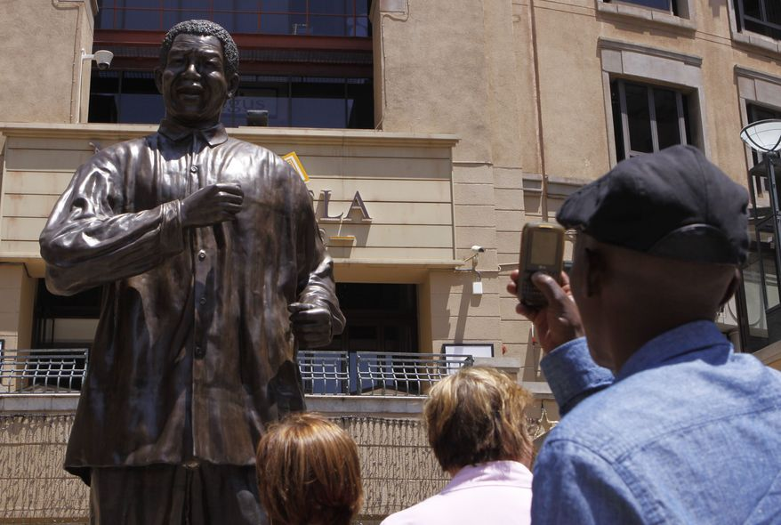 People take photos of the giant statue of former South African President Nelson Mandela in Mandela Square in  Johannesburg on Sunday, Dec. 9, 2012. South Africans prayed for Mr. Mandela's health and anxiously awaited further word about the 94-year-old anti-apartheid leader after he was admitted to a military hospital on Saturday. (AP Photo/Denis Farrell)