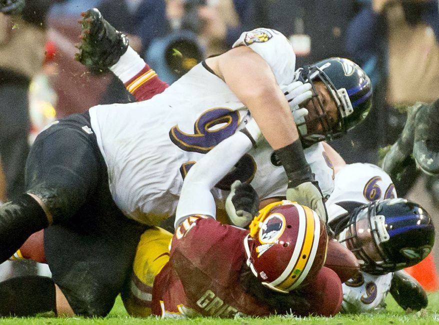 Redskins quarterback Robert Griffin III suffered a sprained knee ligament on this hit by Baltimore tackle Haloti Ngata. Griffin is listed as day to day as Washington looks to extend its winning streak to five games. (Andrew Harnik/The Washington Times)