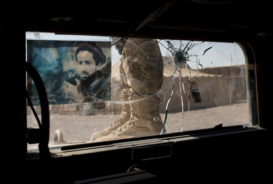 In this Friday, Oct. 19, 2012 photo, a member Afghanistan's elite Civil Order Police stands next to a bullet damaged windsheild of his armored vehicle after coming back from a patrol in Marjah, southern Helmand province, Afghanistan. The window is decorated with a picture of Afghanistan's famed anti-Taliban warrior Ahmed Shah Masood. (AP Photo/Anja Niedringhaus)