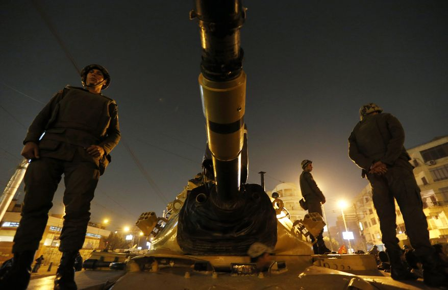 Egyptian soldiers stand guard atop a tank in front of the presidential palace in Cairo on Sunday, Dec. 9, 2012. (AP Photo/Petr David Josek)