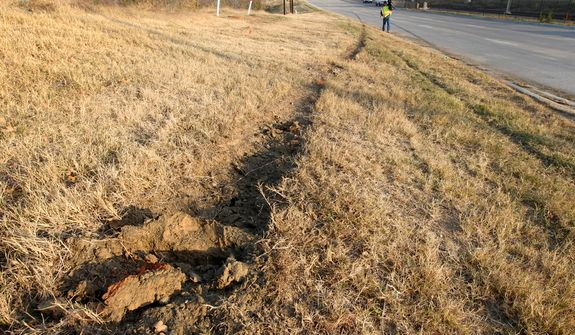 Tire ruts are seen on the ground with skid marks as a news cameraman (rear) films the area at the site of a single-vehicle accident involving Dallas Cowboys player Josh Brent on Dec. 8, 2012, in Irving, Texas. Brent is facing an intoxication manslaughter charge after the accident killed teammate Jerry Brown, a linebacker on the team's practice squad. (Associated Press)