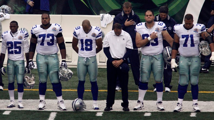 Dallas Cowboys players hang their heads prior to their game against the Cincinnati Bengals on Dec. 9, 2012, in Cincinnati, during a moment of silence for teammate Jerry Brown, who was killed in an automobile accident. (Associated Press)