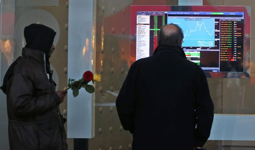A man checks a monitor with stock exchange data as a flower seller approaches him in Milan, Italy, on Dec. 10, 2012. (Associated Press)