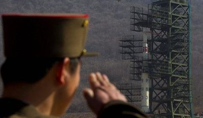 **FILE** A North Korean soldier salutes in front of the country's Unha-3 rocket, slated for liftoff between April 12-16, at Sohae Satellite Station in Tongchang-ri, North Korea, on April 8, 2012. (Associated Press)