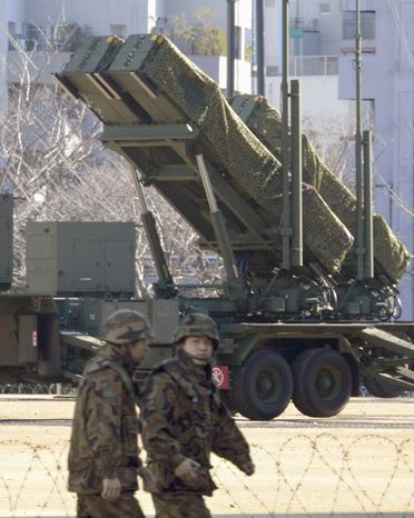 Japan's Ground Self-Defense Force members walk by a ground-based Patriot Advanced Capability-3 interceptor deployed to prepare for North Korea's planned launch of a long-range rocket at the Defense Ministry in Tokyo on Dec. 10, 2012. (Associated Press/Kyodo News)