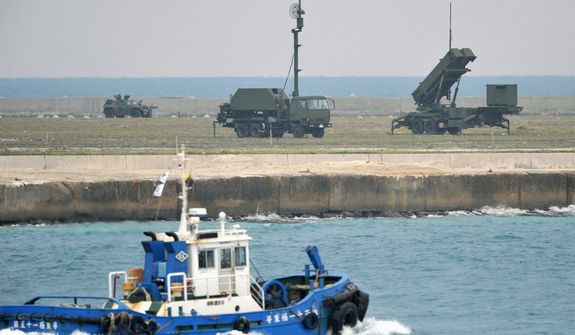 A fishing boat sails by a ground-based Patriot Advanced Capability-3 interceptor (right) and other vehicles deployed to prepare for North Korea's planned launch of a long-range rocket at a port in Ishigaki on Ishigaki Island, Okinawa Prefecture, southwestern Japan, on Dec. 10, 2012. (Associated Press/Kyodo News)